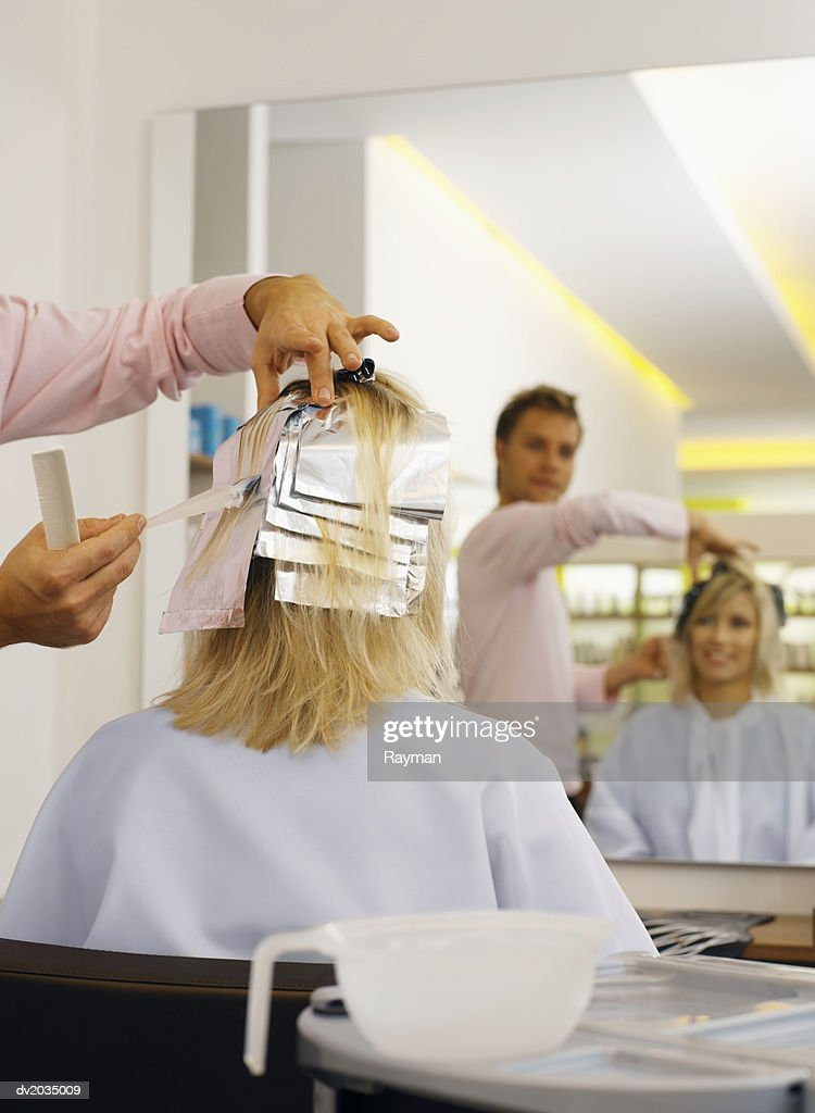 Hairdresser Applying Hair Dye to a Woman's Hair : Stock Photo
