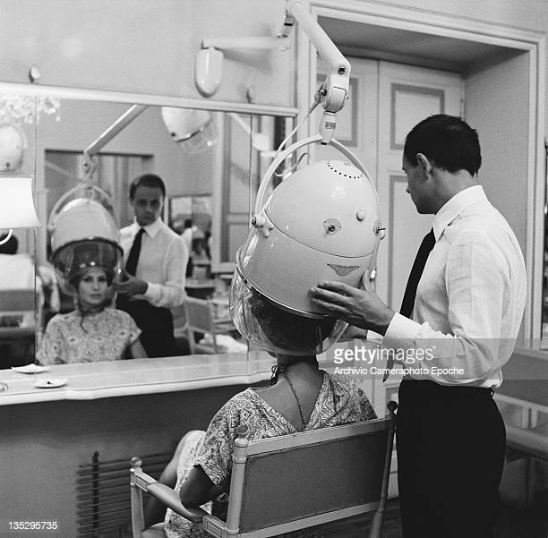 A hairdresser attends to a customer at his salon in Rome circa 1967