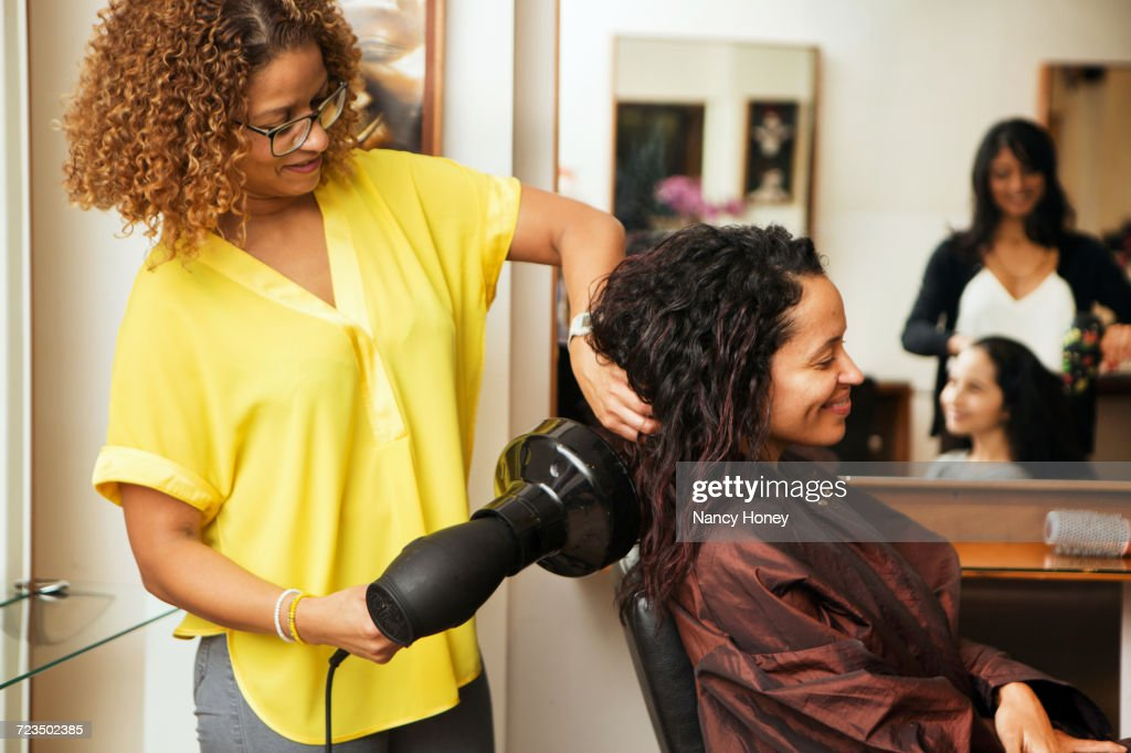 Hairdresser blow drying female customers hair in hair salon : Stock Photo