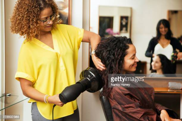 hairdresser blow drying female customers hair in hair salon - black hair stock pictures, royalty-free photos & images