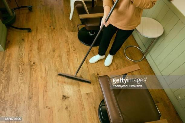hairdresser cleaning floor in his beauty shop. - 掃く ストックフォトと画像