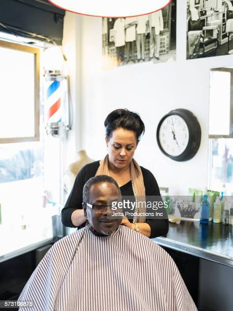 Hairdresser clipping hair of man in retro barbershop