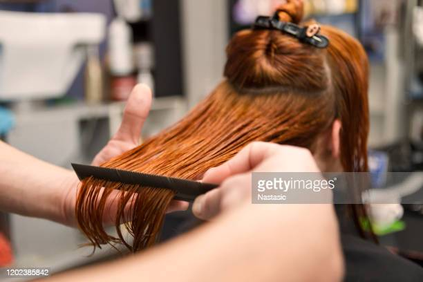 hairdresser combing wet hair of a redhead woman - redhead stock pictures, royalty-free photos & images