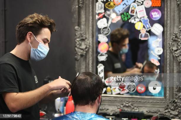 Hairdresser cuts a clients hair at Swyd barber and tattoo parlour in Cardiff, south Wales on October 20 ahead of a short, two-week lockdown due to...