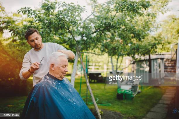 Hairdresser cuts hair to his father