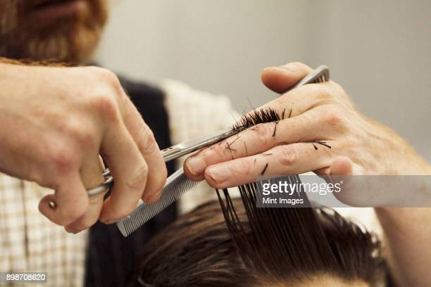 A hairdresser cutting a mans hair, close up.