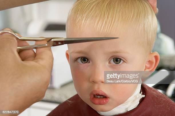 Hairdresser cutting boy's hair