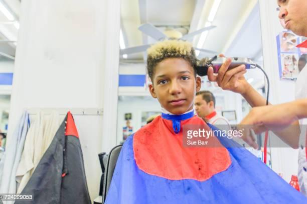 Hairdresser cutting teenage boys hair in barbershop