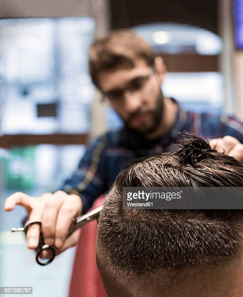 Hairdresser cutting young mans hair in a barbershop