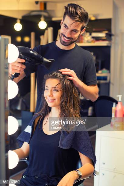 hairdresser drying hair of pretty happy young woman - parrucchiere foto e immagini stock