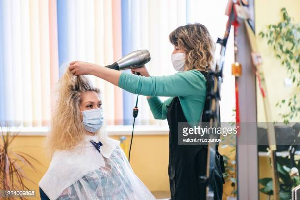 hairdresser drying woman's hair with hair dryer in beauty studio, during covid -19 - hairdresser stock pictures, royalty-free photos & images