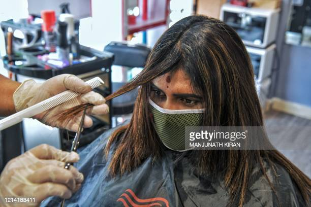 Hairdresser gives a haircut to a customer at a women's beauty parlour after the government eased the nationwide lockdown previously imposed against...