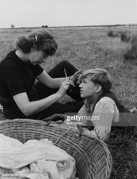 Hairdresser Helen Penfold with child actor Anthony Wager during location filming for director David Lean's film adaptation of Dickens' novel 'Great...