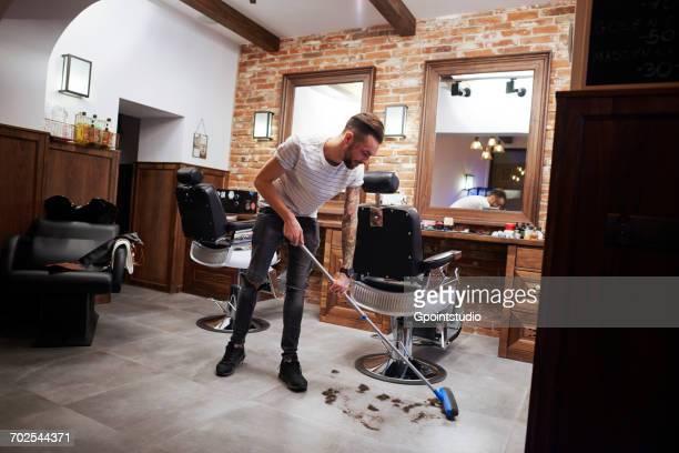 Hairdresser in barber shop sweeping up hair