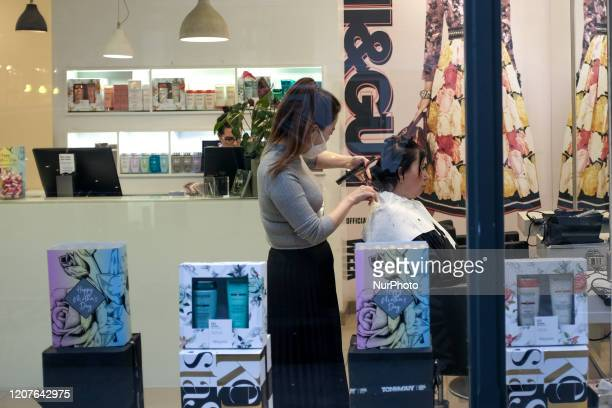 A hairdresser is seen at work as she wears a surgical mask as the Government recommends that people avoid social contact during the ongoing COVID19...