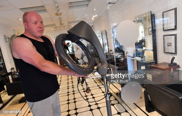 Hairdresser John Belfield prepares his hair salon adapted with perspex screens in between customers' seats in light of the COVID19 pandemic in...