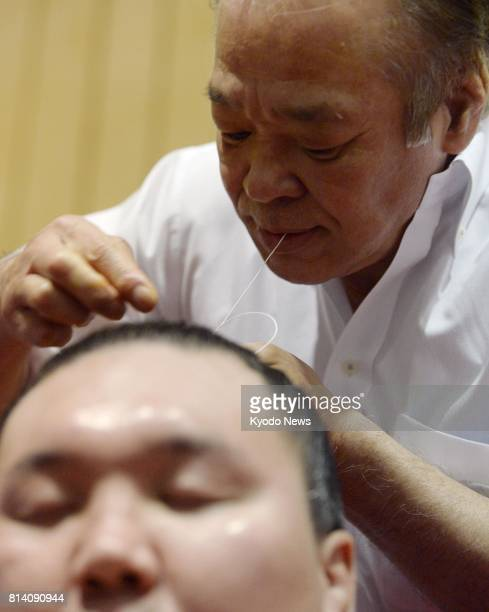 A hairdresser makes a topknot for Hakuho after a bout at the Aichi Prefectural Gymnasium on July 12 the fourth day of the 15day Nagoya Grand Sumo...