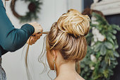 Hairdresser makes complex and beautiful hairstyle upper bun. Suitable for evening and wedding style