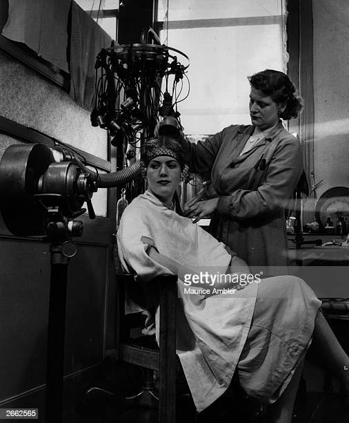A hairdresser perms a woman's hair using an oldstyle perming machine and hairdryer Original Publication Picture Post 7256 Half A Century Of Perms pub...