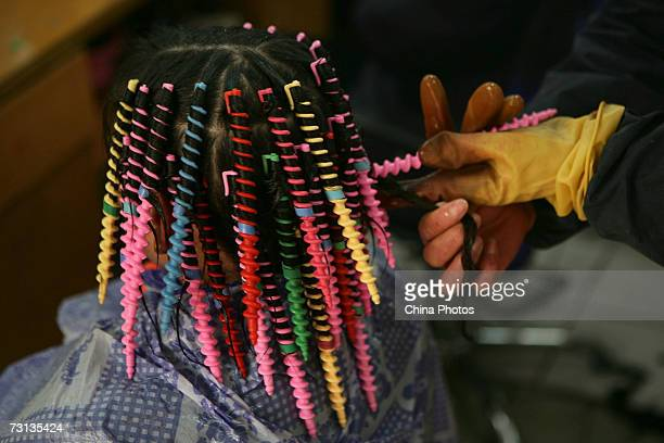 A hairdresser perms hair for a woman in a salon at the Shibati Area on January 27 2007 in Chongqing Municipality China The Shibati Area is a very old...