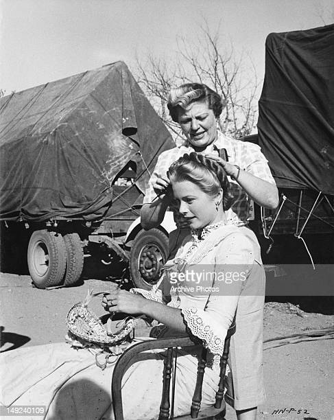 Hairdresser prepares American actress Grace Kelly for a scene in the western 'High Noon', circa 1951.