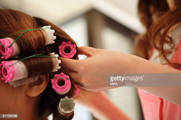 hairdresser putting curlers in customer's hair - permed hair stock photos and pictures
