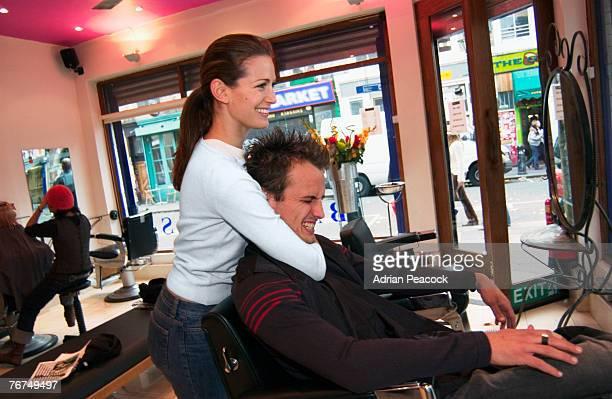 Hairdresser putting man in headlock