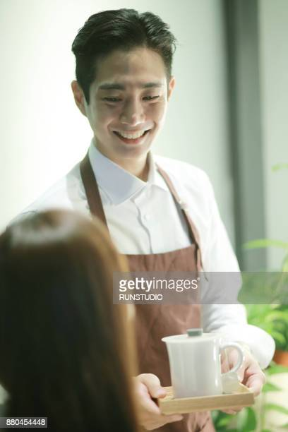 Hairdresser serving coffee to customer