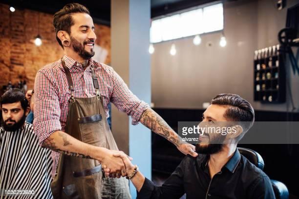apertando a mão do cliente no salão de cabeleireiro - homens de idade mediana - fotografias e filmes do acervo