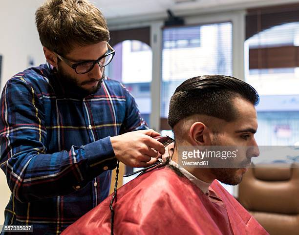Hairdresser shaving young mans hair in a barbershop
