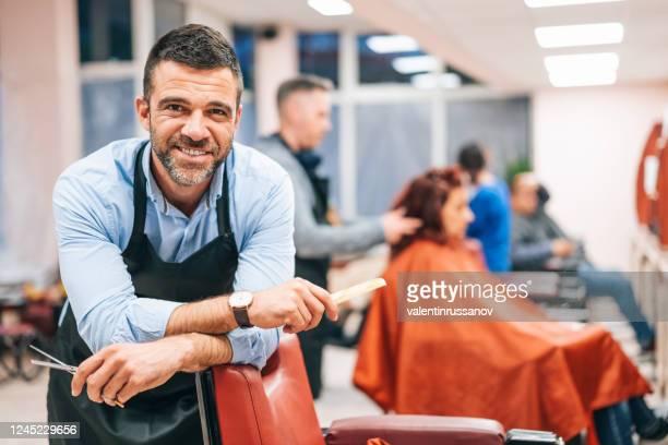 parrucchiere si trova in uno studio di parrucchiere - salone di parrucchiere foto e immagini stock