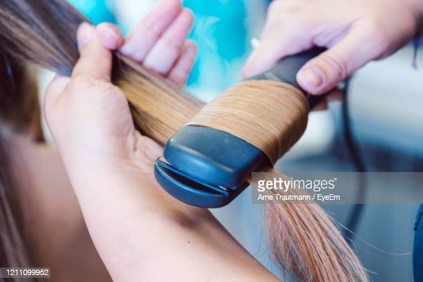 hairdresser straightening hair of woman customer - adjusting stock pictures, royalty-free photos & images