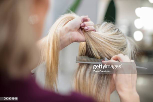 hairdresser styling customer's hair in salon - hair salon stock pictures, royalty-free photos & images