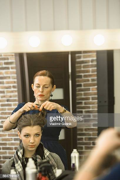 Hairdresser styling models hair in studio