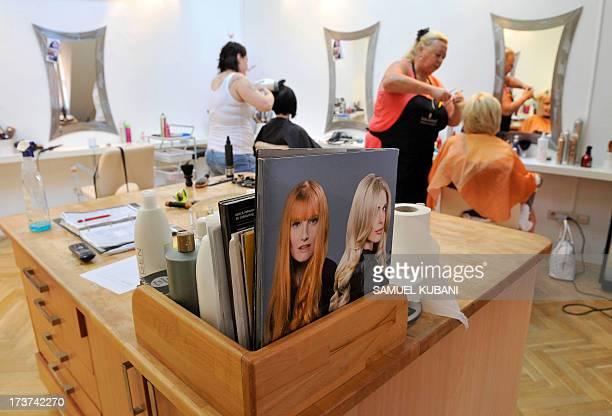 Hairdresser trim the hair of customers at a women's barbershop in Bratislava, Slovakia on July 17, 2013. AFP PHOTO/SAMUEL KUBANI