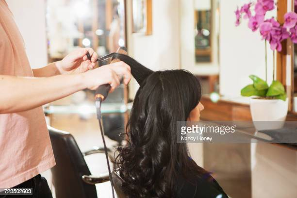 Hairdresser using curling tongs on customers long black hair in salon