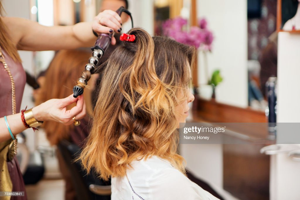 Hairdresser using curling tongs on customers long brown hair in salon : Photo