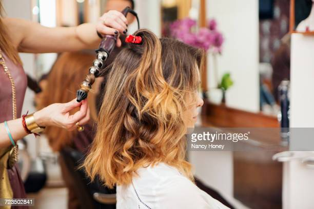 Hairdresser using curling tongs on customers long brown hair in salon