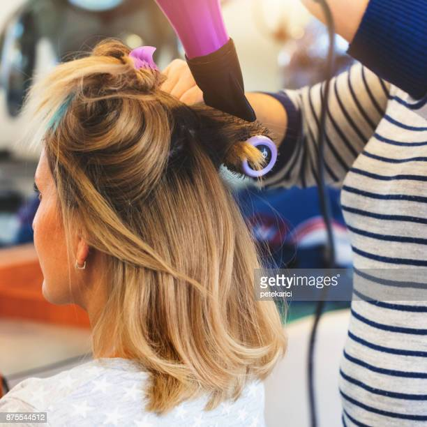 hairdresser using hairbrush and hair dryer - highlights hair stock pictures, royalty-free photos & images