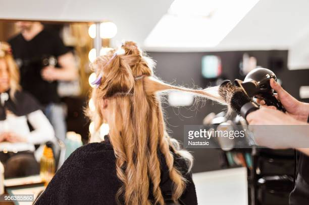 hairdresser using hairdryer - hairstyle stock pictures, royalty-free photos & images