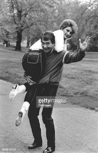Hairdresser Vidal Sassoon lifts model Francesca Thyssen in Hyde Park, London. Both wear jeans from his 'Active Sports' range, on sale at his new...