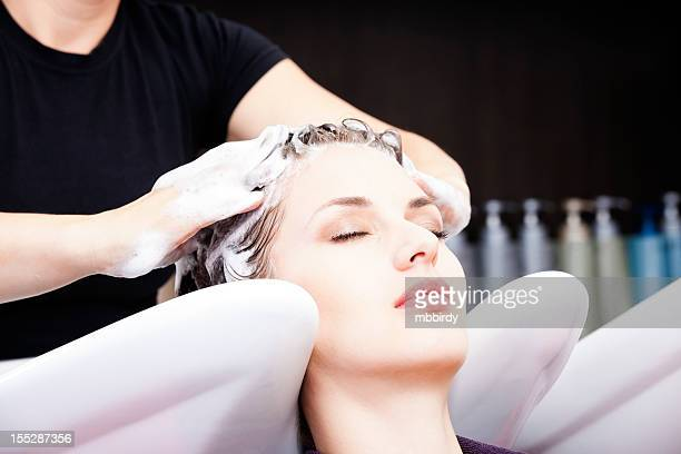 Hairdresser washing woman's hair after coloring