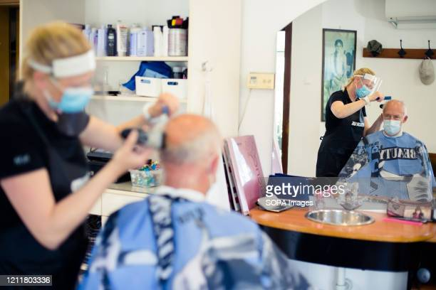 Hairdresser wearing a face mask and shield as preventive measure cuts hair of a client amid coronavirus crisis. Hair salons, restaurants along with...