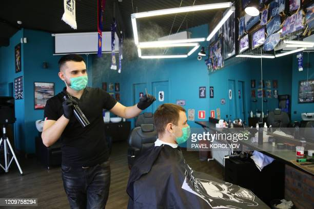 A hairdresser wearing a face mask gives a client a haircut at a barber shop in Vladivostok on April 12 amid the COVID19 pandemic caused by the novel...