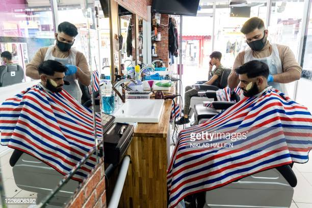 Hairdresser wearing a face mask or covering due to the COVID-19 pandemic, cuts a customer's hair at 'Khan-Master's Hairdressing' in Peckham, south...