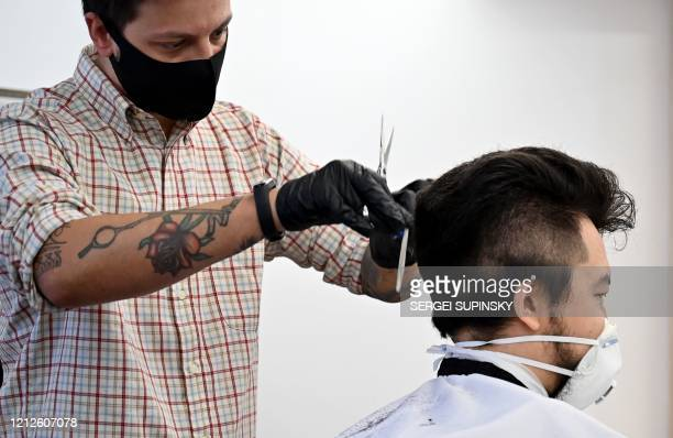 A hairdresser wearing a protective face mask cuts the hair of a client as the barber shop reopened on May 11 in Kiev after monthslong closures aimed...