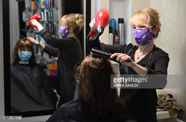 A hairdresser wearing a protective face mask cuts the hair of a client as the hairdressing salon reopened on May 11 in Kiev after monthslong closures...