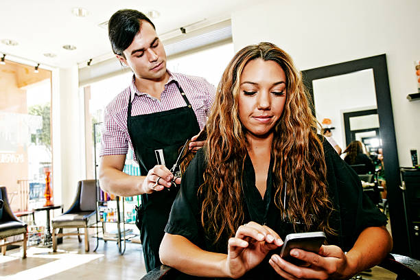 hairdresser with customer texting on cell phone in hair salon picture id672162247?k=20&m=672162247&s=612x612&w=0&h=wFsYvvLEcfMPAiwwhT33azYeozdhioMlPNT0RUpMz 0=