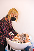 hairdresser with face protection mask washing