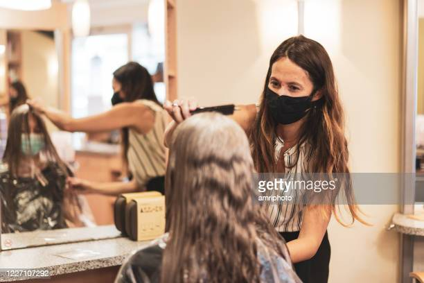 hairdresser with mask enjoying to work again in her hair salon after lockdown is over - parrucchiere foto e immagini stock